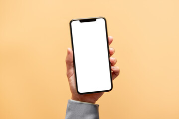 Smartphone mockup. Close up hand holding black phone white screen on yellow background. Mobile phone frameless design concept.