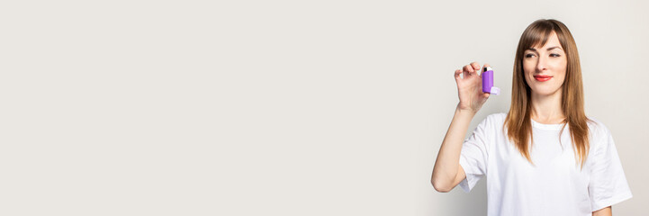 happy young woman holds an inhaler in her hand, looks at the inhaler on a light background. Banner....
