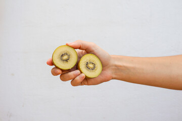 Hand holding a sliced yellow kiwi isolated on white wall.