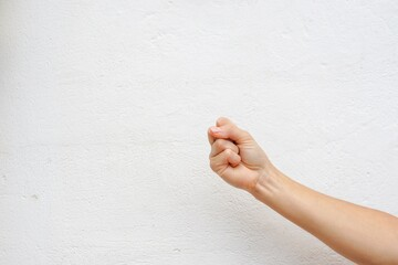 Hand clenching the fist isolated on a white wall texture.