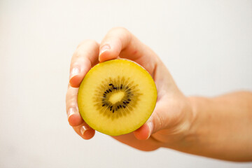 Detail of a hand holding a yellow kiwi isolated on white.