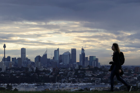 A woman walks on a hill overlooking the city centre skyline in Sydney
