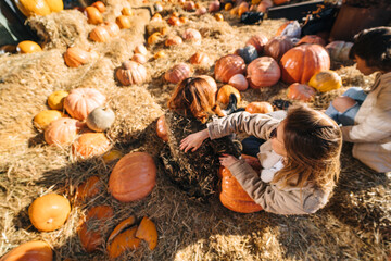 Young girls lie on haystacks among pumpkins.