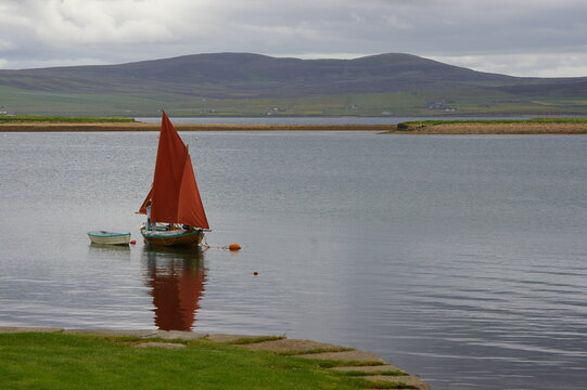 A small yacht with red sails moored at Stromness, Orkney islands, Scotland, UK.