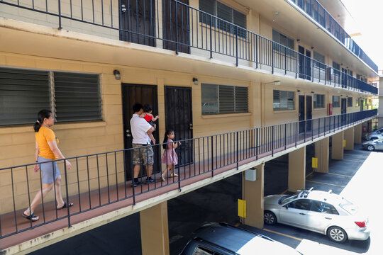 Judith and Jose Ramirez walk with their daughters to their unit in an apartment complex in Honolulu