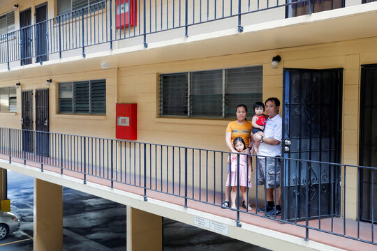 Judith and Jose Ramirez pose with their daughters outside their unit at an apartment complex in Honolulu