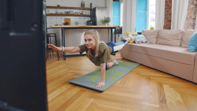 Young woman doing exercises at home watching sport video