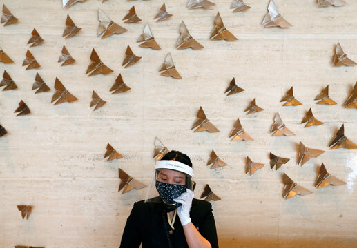 A receptionist staff wearing a face shield and a protective mask uses a phone at the lobby of The Margo Hotel, following the coronavirus disease (COVID-19) outbreak in Depok