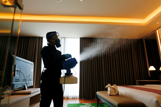 Staff silhouette wearing a face shield and protective mask sprays disinfection at the room of The Margo Hotel, following the coronavirus disease (COVID-19) outbreak