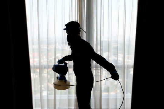 Staff silhouette wearing a face shield and protective mask carries disinfection at the room of The Margo Hotel, following the coronavirus disease (COVID-19) outbreak in Depok