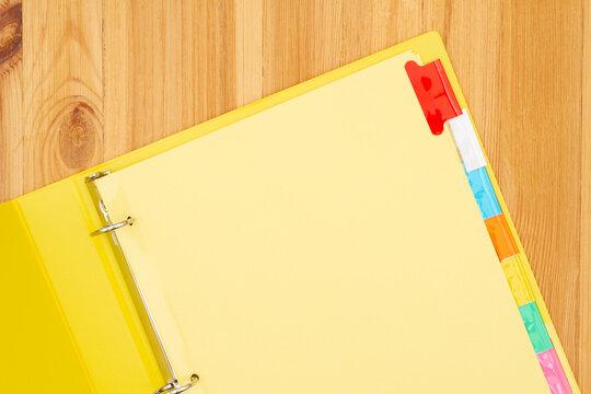 Blank file tabs in a yellow binder on wood desk mockup