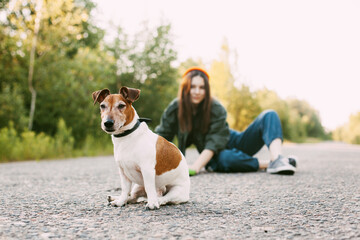 The dog is sitting in front of the girl on the road. A young girl with her pet resting while walking in nature. Blurred background, space for text