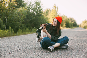 A charming teenage girl in an orange hat sits with her dog on the road. The girl hugs her pet. Friendship, care. Space for text