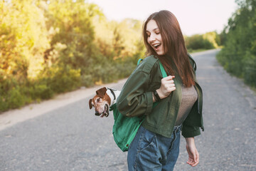 A beautiful girl is holding a green backpack on her shoulder, from which a cute dog looks out. A girl and her friend travel together, take walks. The concept of friendship and care