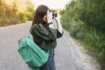Cute brunette looks at the camera lens. A girl photographs nature. Side view, space for text