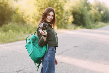 A beautiful girl with a camera in her hands is walking along the road in search of interesting shots. The girl travels and takes photos of landscapes on a vintage camera. Space for text