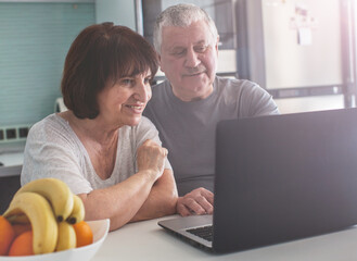 Elderly couple looking at computer in the kitchen