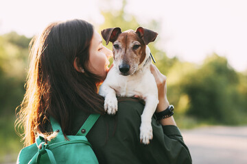 A young girl in a jacket with a green backpack on her shoulders holds a dog in her arms and hugs her. The girl walks with her pet. Rear view, place for text.