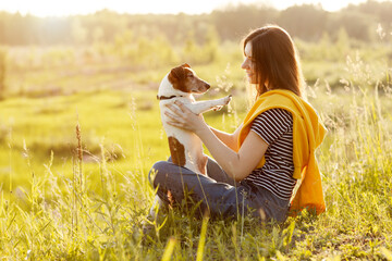 A young girl Sits on the grass in the rays of the setting sun and holds her dog in her arms. Dog walking. Friendship, care, place for text