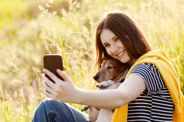 An attractive teen girl takes photos of herself and her dog using a mobile phone camera. A girl takes a photo while walking with her pet