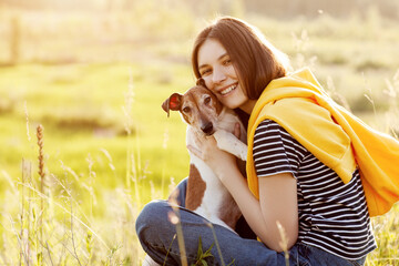 A charming girl is sitting on the grass, smiling and hugging her dog. A girl and her pet are relaxing in the fresh air. Friend, friendship, care