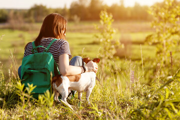 A dark-haired girl with a green backpack on her back and a striped t-shirt hugs a dog and sits on the grass in a meadow. A girl is resting with her pet after a walk. Back view, space for text