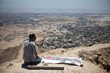 "Eitan Melet, a director at Israeli lobby ""Safeguarding Eternity"" sits next to a map near ruins of the ancient desert fortress of Cypros, overlooking the Palestinian city of Jericho, in the Israeli-occupied West Bank"