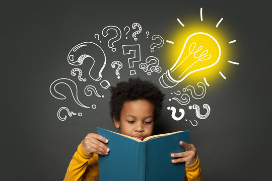 Intelligent black kid student reading book and having idea. Brainstorming and idea concept
