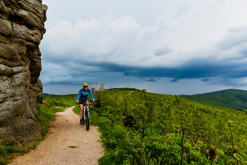 Wall Mural - Cycling woman on mtb bike on gravel mountain road, Beskidy, Poland.