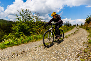Cycling woman on mtb bike on gravel mountain road, Beskidy, Poland.