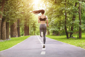 Sport Motivation. Rear View At Athletic Girl Jogging On Path In Park