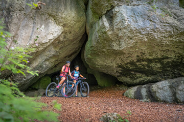 Grandmother and granddaughter riding their mountainbikes in the rocky landscape of Frankonian Switzerland in Bavaria, Germany
