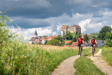 grandmother and granddaughter riding their mountain bikes in front of the awesome skyline of Hiltpoltstein in Frankonian Switzerland, Bavaria, Germany
