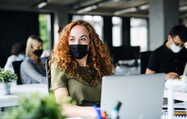 Young woman with face mask back at work in office after lockdown.