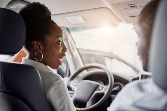 black married family examining car from inside, they are checking convenience and look characteristics of automobile in dealership, want to buy it