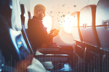 Hipster man watching video on mobile phone, while enjoying flight in air plane during his vacations trip. Male listening to music in headphones. Infographics elements of multimedia content on gadgets