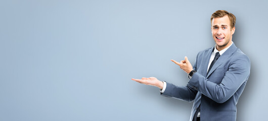 Portrait image of businessman showing, holding or giving something standing over grey background. Copy space area for some text. Success in business, job and education concept. Wide banner composition