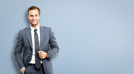Portrait image of happy smiling confident businessman in grey suit and tie, standing against grey background with copy space for some text. Business success concept picture.