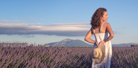 Summertime in lavender. Young beautiful woman in lavender flowers field at sunset in white dress....