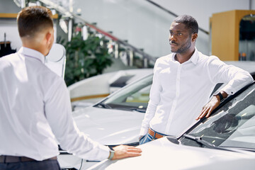 confident professional salesman talk about characteristics of car to customer man, black business...