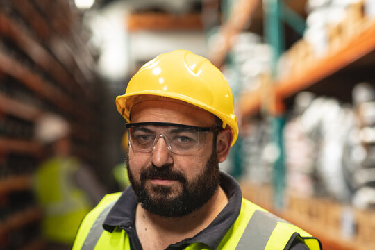 Portrait of a male factory worker wearing a safety helmet and glasses