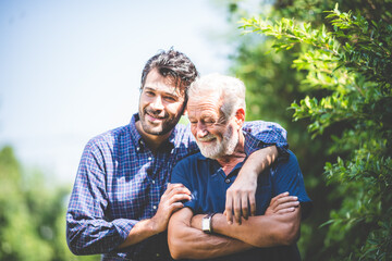Fototapeta happy hipster adult son and senior father hugging at home, concept of stay at home with family obraz