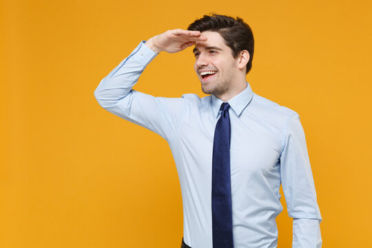 Smiling young business man in classic blue shirt tie isolated on yellow background. Achievement career wealth business concept. Mock up copy space. Holding hand at forehead looking far away distance.