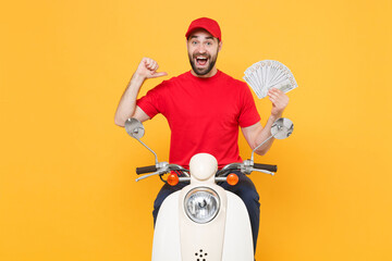 Delivery man in red cap t-shirt uniform driving moped motorbike scooter hold cash money isolated on...