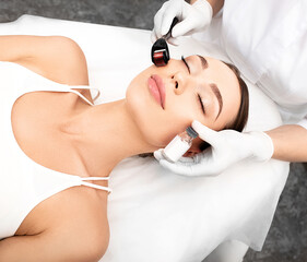 Beautician doing skin treatment using a microneedle derma roller. Woman getting procedure skincare,...