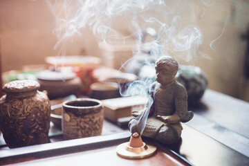Fgurine King of monkey sitting with spoon on light fabric and dark wooden table and meditete with chinese incense