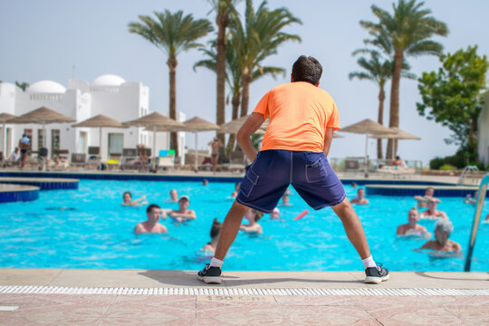Sharm El Sheikh, Egypt - March 07, 2020: The trainer does an aqua gym class in the pool of an expensive hotel. The animator entertains vacationers with exercises in the water