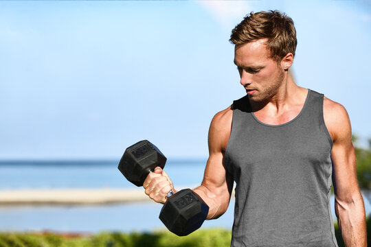 Bicep curl free weights training fitness man outside working out arms lifting dumbbells doing biceps curls. Fit man arm exercise workout exercising arms with dumbbell weight at outdoor beach gym.