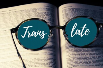 Closeup shot of a pair of glasses on a book with translate text