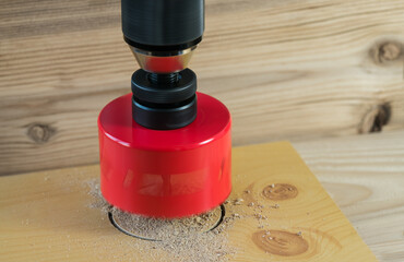Rotating hole saw with pilot drill bit on a wooden background. Closeup of red steel holesaw. Drilling of annular bore into pressed wood by sharp cutting tool with motion blur and sawdust. Woodworking.